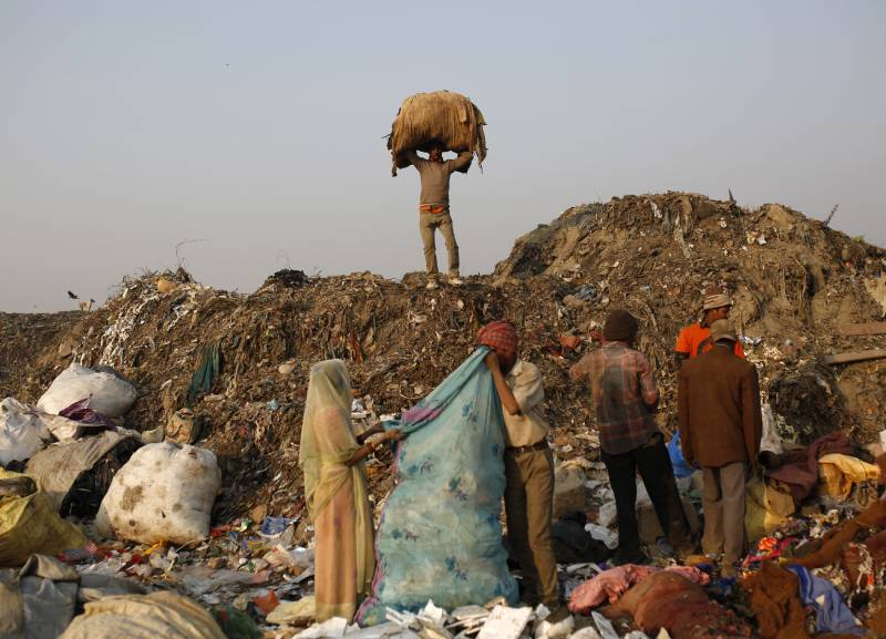 Rag pickers collect recyclable material at a garbage dump in New Delhi November 19, 2014. REUTERS/Ahmad Masood (INDIA - Tags: SOCIETY BUSINESS EMPLOYMENT ENVIRONMENT)