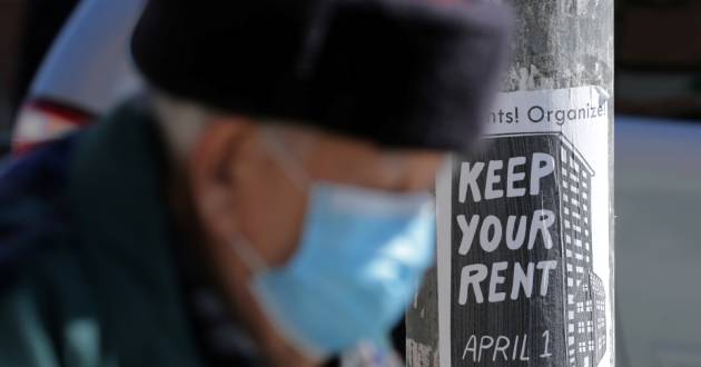 An elderly man wearing a protective face mask passes a sign publicizing a rent strike during the global outbreak of the coronavirus disease (COVID-19) in Toronto, Ontario, Canada April 6, 2020. REUTERS/Chris Helgren/File Photo