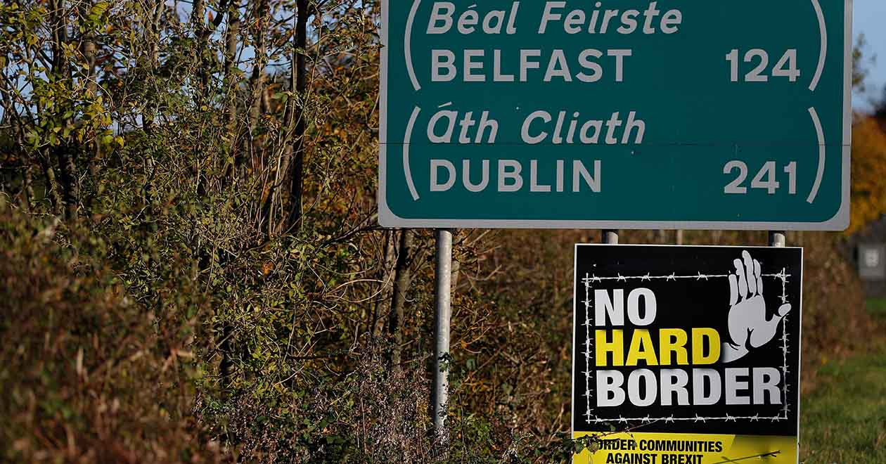 Irish border: A 'No hard Border' poster is seen below a road sign on the Irish side of the border between Ireland and Northern Ireland near Bridgend on 16 October 2019. REUTERS/Phil Noble