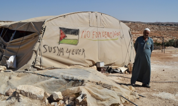 Mohammed Nawjaa of the Susiya community in front of a tent