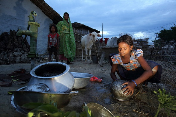 Nepalese girl washing utensils