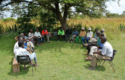 Healthy conversation: a group of men discuss the taboo of widow  cleansing and (left)former cleanser Esban Ochanga.
