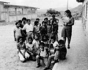 Children at the San Martin school to the north of Ocotal, with teacher Judith Ponce. The building to the left is the new school on which construction had to be halted because of a shortage of materials. On the right is their current classroom.