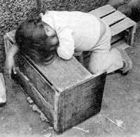 Alone and vuinerable on the street. A Peruvian child, separated from her parents in a busy marketplace, falls into an exhausted sleep.