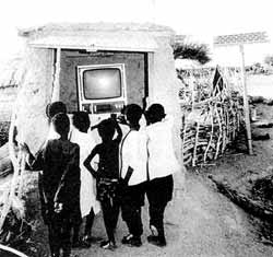 Like us, Third World people are often eager to have consumer goods: indulging in TV in Niger (pictured) and buying taped music in Indonesia.