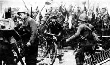 Jim Graham tentatively wheels his bicycle through Shanghai during the Japanese invasion.