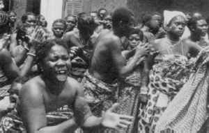 Spirit of fervour. At a ritual healing ceremony in Ghana, people dance and chant so as to frighten an evil spirit out of a woman's body.