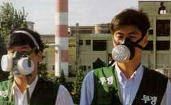 Poisoned! Wonjin Rayon workers return with gas masks and protest vests to their deserted factory.
