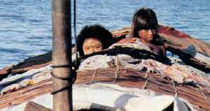 On open water in the harsh sun young women use rice paint
