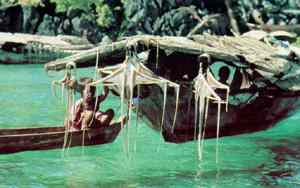 Resting on their boats in a calm harbour the sea npmads hang freshly-caught squid across bamboo rods to dry.