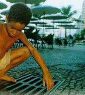 Beneath the tables of a smart Rio cafe a child searches for coins in the drains. Photo by JOHN MAIER/STILL PICTURES