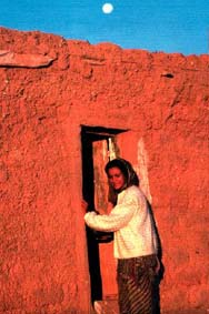 Knocking on the door of liberation. Metou Ehel Never (seen entering her family's one-room home just after dawn) is part of a new generation of assertive Saharawi women.