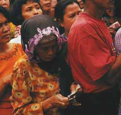 Counting the cost of ecomonic chaos in a queue for rice in Jakarta, Indonesia.
