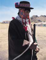 Rufino and his gun, with the village's strange new housing development in the background.