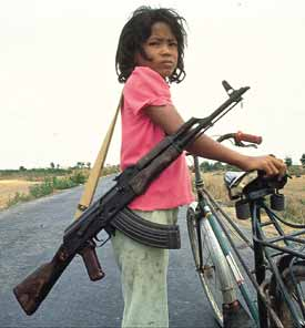 Girl with bicycle and Kalashnikov in Cambodia.