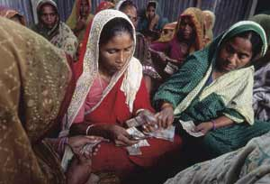 Eyes down for the pay-out: village women counting the small amounts they have borrowed from the Grameen Bank. Most microcredit loans are taken out by women.