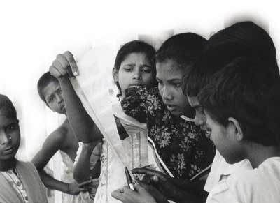 Passion for pictures. Rabeya studies negatives while Moli, Iqbal and Shefali look on. Inset are photos of Shahidul Alam with a new group of children from a village in Brahmanbaria – the 'Out of Focus' children are helping to teach them photography.