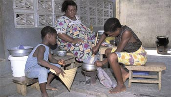 Keeping the home fires burning: domestic workers in Togo prepare a meal under their mistress's watchful gaze.