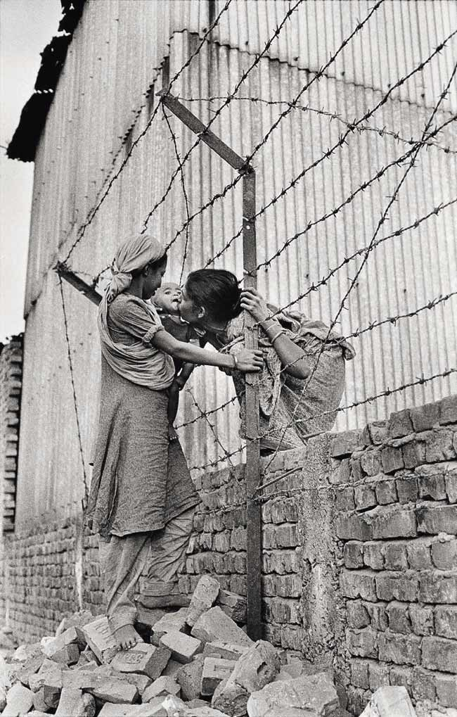 --Mother and daughter brick breakers meet through barb wire-- Photo © GMB Akash, Fatulla, Bangladesh.