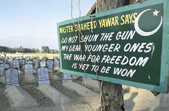 Beckoning death: a sign in a Kashmiri cemetery urges young people on to martyrdom.