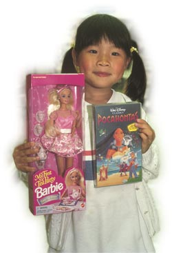 Rushing to grow up: a young consumer with a Barbie doll in a Hong Kong toy store.