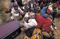 Tears and lamentations: a coffin is lowered into the earth in one of Lusaka's aids cemeteries.