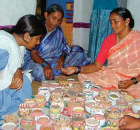 Mother and daughter with a treasure-trove of local crop varieties (pictured); Coloured powder used as markers in seed selection meetings (left).