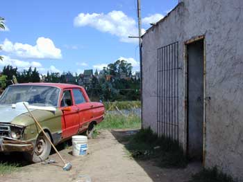 A dying Ford Falcon in La Matanza ('The Slaughter'). During the Dirty War this vehicle became notorious, used by the military to prowl the streets, pick up dissidents and 'disappear' them. Only the front remains in the original khaki - the other half has since been painted a defiant red. Overlooking it, in the background, is the Disneyesque skyline of the crazed oligarch's Neverland, which is said to contain a complete steam train.