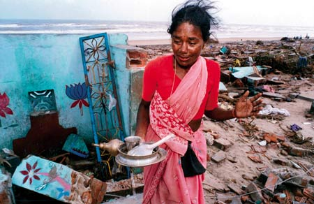 Utter desolation: an Indian woman recovers the few possessions remaining in the ruins of her home in Tamil Nadu. Photo: Dieter Telemans / Panos
