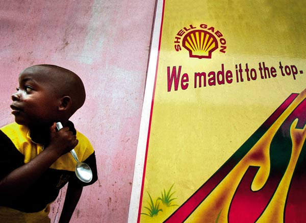 Boy by Shell billboard, Gabon Around Shell's terminal in Gabon is an important nature reserve, supposedly protected by its national park status. Most people here work for Shell, but the oil reserves are running out. When they do, people may be forced to turn to logging and hunting within the reserve. In 2000, fossil fuels like oil accounted for 77 per cent of world energy consumption. The environmental costs of conventional energy production and use include air, soil and water pollution, as well as acid rain and loss of biodiversity. Photo: Sven Torfinn / Panos