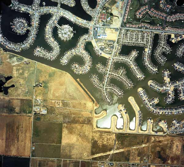 Homes on reclaimed wetland, California, US Draining, filling and conversion to farmlands or cities destroyed an estimated half of the world's wetlands in the 20th century. Photo: NRSC / Still Pictures