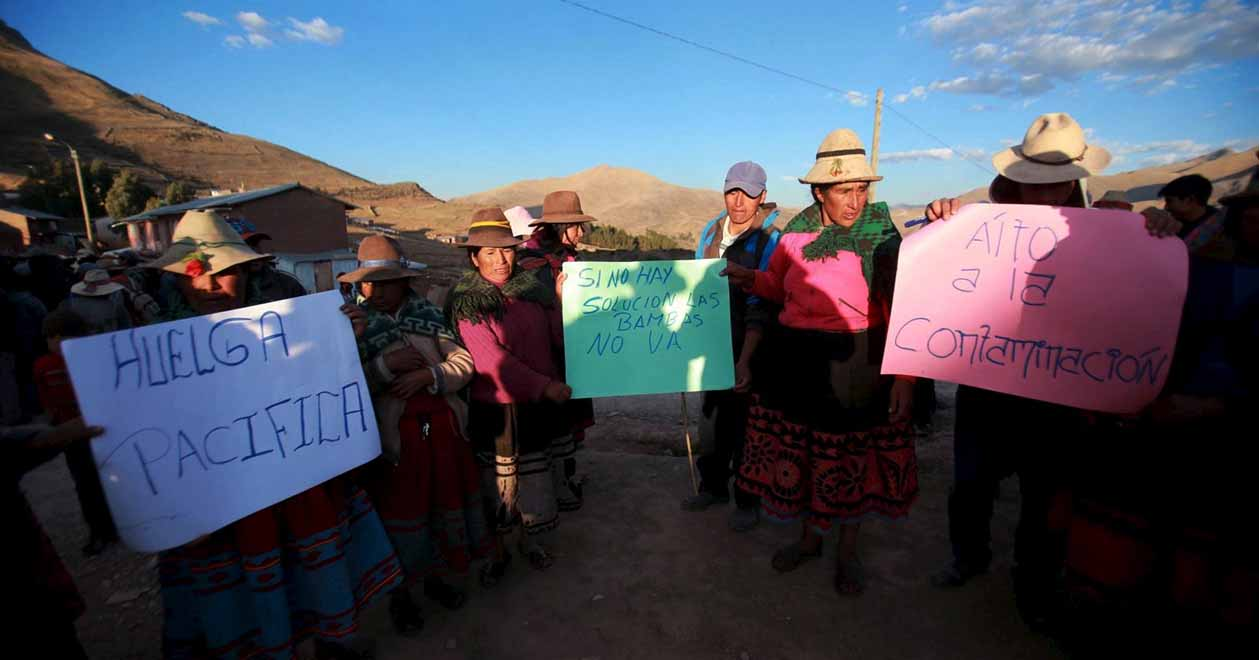Residents hold signs during a protest against Las Bambas mine in Apurimac, where Virginia Pinares also fights