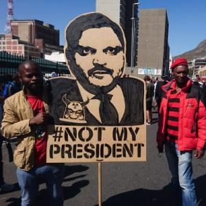 'Zuma must fall' protesters with a banner depicting Atul Gupta, implicated in recent scandals. Pic: Discott, CC-BY-SA4.0