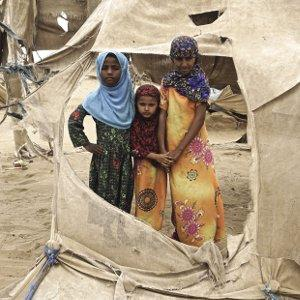 Three displaced Yemeni girls stand by the shredded remains of their tents in Abs settlement, which is regularly damaged by passing sandstorms.