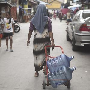 A drinking water vendor sets off, looking for customers in Jakarta's poorest neighbourhoods. Photo: Solo Imaji/Barcroft Media via Getty
