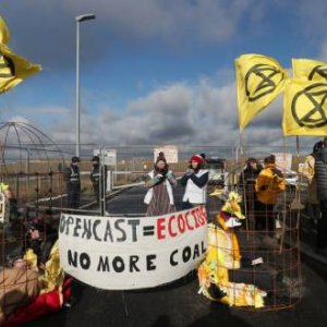 Extinction Rebellion demonstrators sit in structures representing 'canary in the coal mine' bird-cages  as others gather during a protest at Banks Group's open-cast coal mine in Bradley, County Durham, Britain February 26, 2020.  REUTERS/Scott Heppell