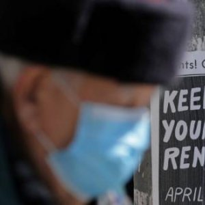 An elderly man wearing a protective face mask passes a sign publicizing a rent strike during the global outbreak of the coronavirus in Toronto, Ontario, Canada April 6, 2020. REUTERS/Chris Helgren/File Photo