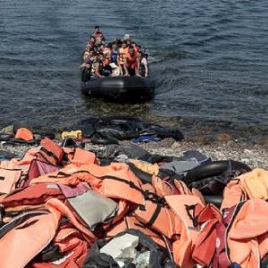 Migrants and refugees arrive by dinghy behind a huge pile of life vests after crossing from Turkey Migrants and refugees arrive by dinghy behind a huge pile of life vests after crossing from Turkey to the island of Lesbos Greece, Sept. 10, 2015.