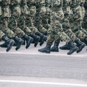 The legs of people wearing camouflage and black boots. They are marching.