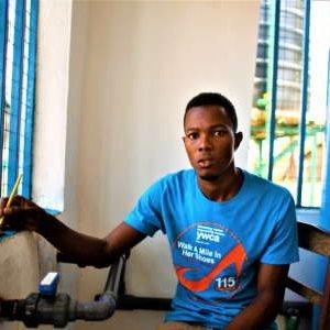 A man wearing a blue t-shirt sits next to a window