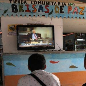 Three former guerrillas watch the election results from La Tienda, the social space in the Icononzo reintegration zone.