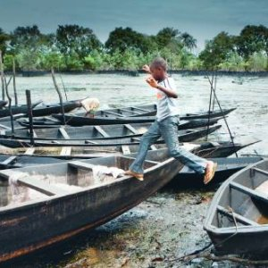 Child's play: A boy jumps across boats wedged on a mixture of crude oil, water and sand, near Bojo in the Niger Delta. Oil production is a major pollutant in the area. Petterik Wiggers/Panos