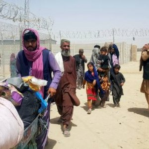 A family from Afghanistan walk next to fence to cross into Pakistan at the Friendship Gate crossing point, in the Pakistan-Afghanistan border town of Chaman, Pakistan September 6, 2021. REUTERS/Abdul Khaliq Achakza