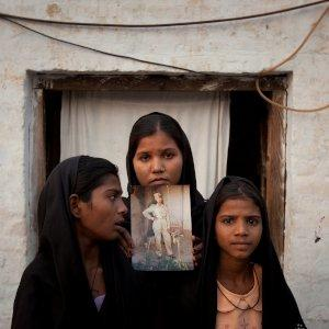 The daughters of Pakistani Christian woman Asia Bibi pose with an image of their mother while standing outside their residence in Sheikhupura located in Pakistan's Punjab Province November 13, 2010. Standing left to right is Esha, 12, Sidra, 18 and Eshum, 10. REUTERS/Adrees Latif