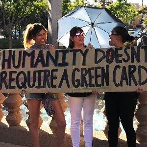 Protesters carry a banner: 'Humanity doesn't require a green card'