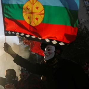 A demonstrator wearing a Guy Fawkes mask waves a Mapuche indigenous flag during a protest against Chile's government in Santiago, Chile October 31, 2019. REUTERS/Henry Romero