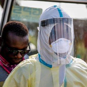 Alfred Kelfala, part of the roving Freetown Ebola burial team, puts on a safety suit before burying a corpse, 2015.