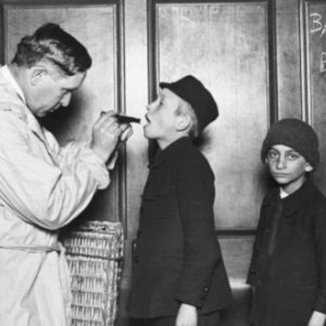 Throughout history migrants have often been treated as a source of disease and 'contagion'. Immigrant children are examined on arrival at Ellis Island, New York, 1911. Credit: Bettmann/Getty