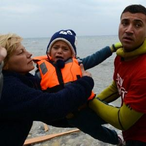 Salam Aldeen handing a child in a life jacket who had been rescued from the dinghy that just arrived to other volunteers. Volunteers take care of the children, until the parents manage one by one to leave the boat and receive back their children. 16 December 2015, Lesbos, Greece.