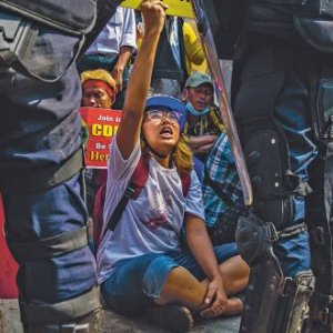 We shall not be moved! Anti-coup protesters remain seated in front of a line of riot police trying to clear roads in Yangon. Partially visible is a poster urging citizens to join the Civil Disobedience Movement.PANOS PICTURES